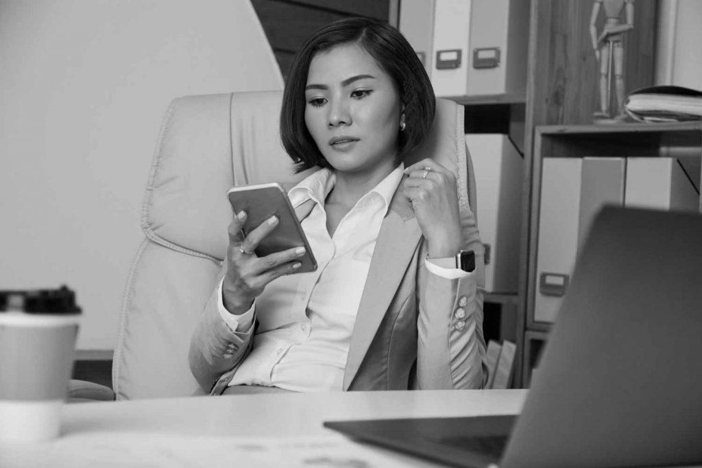 Eine Dame konzentriert sich auf ihr Smartphone, um ihren Social Media Auftritt zu planen